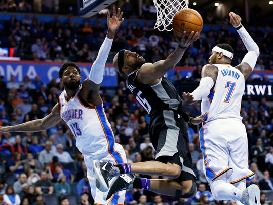 Sacramento Kings guard Vince Carter (15) shoots between Oklahoma City Thunder forwards Paul George (13) and Carmelo Anthony (7) in the first half of an NBA basketball game in Oklahoma City, Monday, March 12, 2018. (AP Photo/Sue Ogrocki)