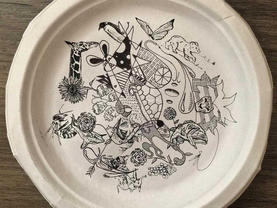 A paper plate serves as the canvas for a piece of Tyler