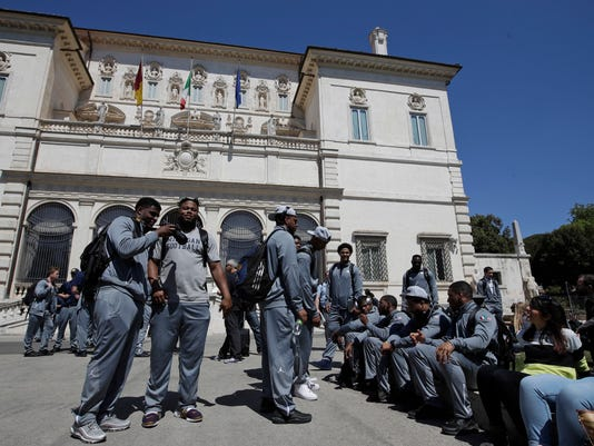 Michigan football team players stand in Rome's Villa Borghese park, Sunday, April 23, 2017. Michigan's football team arrived in Rome this weekend and kicked off the unique trip by meeting with refugees before going to the Vatican for a Papal address and practicing a few times. (AP Photo/Alessandra Tarantino)