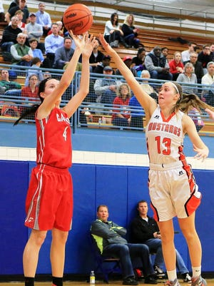 Canton's Erin Hult (left) launches a jumper over the outstretched arms of Northville defender Jessica Moorman.