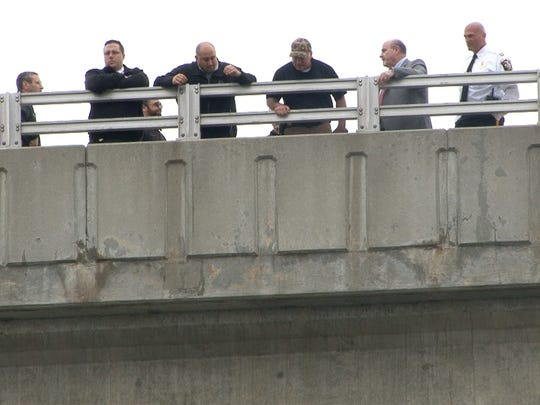Police officers look on from the Route 35 southbound side bridge in Neptune into the Shark River below Friday, April 21, 2017.  This is near the site where Sarah Stern was alledgedly thrown off the bridge and into the river.