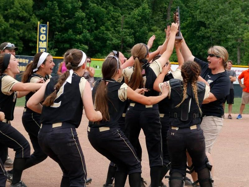 Holt players rush to coach Kim Reichard, right, and their district championship trophy after defeating Jackson 16-0, Saturday, June 4, 2016, at Grand Ledge High School.