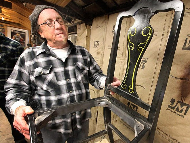 Craig Smith, creative genius behind Frankenstein Furniture, shows off a chair he designed at his SoBro shop.