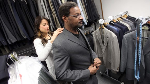 Star Lotta, founder of Suiting Warriors, helps fit Army veteran Joseph Taylor with a new suit, Wednesday on March 12, 2014.