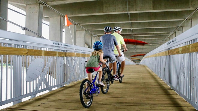 Third Ward Alderman Chad Tuneberg, his son, Mats, and daughter, Melaina, ride across the rebuilt footbridge under the Jefferson Street bridge on Monday. The walkway was closed in 2015 for safety concerns.