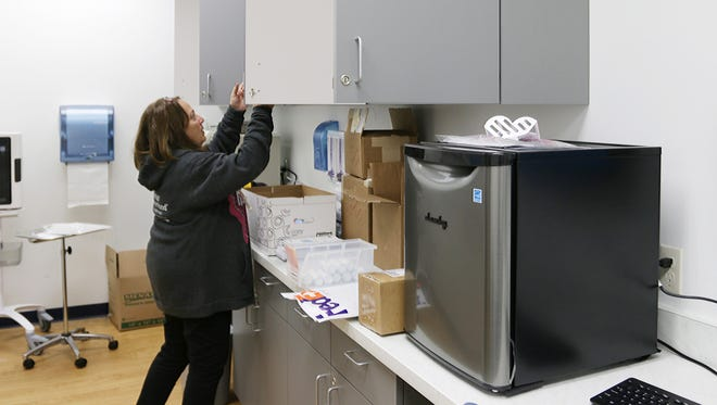 Kris Zastrow, a regional Planned Parenthood director, arranges a shelving area in a lab at a new clinic in Sheboygan.