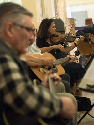 Ramona Connelly joins other musicians at the Pensacola Folk Music Society's jam at Artel Gallery Wednesday, March 7, 2018.