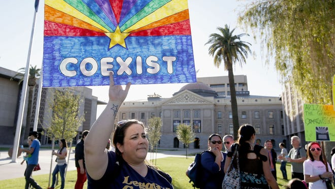 Jo Beaudry holds up a sign as she joins nearly 250 gay rights supporters protesting SB 1062 at the Arizona Capitol.