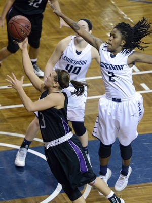 USF's Taylor Varsho takes a shot in front of Concordia-St. Paul's Anika Whiting and Ameshia Kearney in Monday's NSIC semifinal game at the Sanford Pentagon, March 3, 2014.  (Elisha Page / Argus Leader)