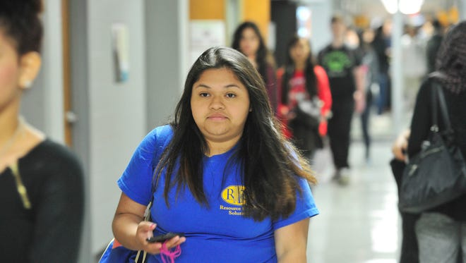 Adriana Herrera, a senior who is undocumented and will not be eligible for Tennessee Promise, walks the hall at Overton High School in Nashville on April 22.