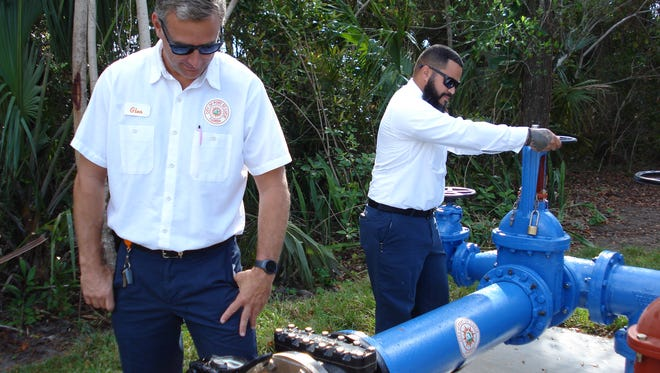 Port St. Lucie Utility Systems employees Glen Cockrell and David Reyes read the meter and open the interconnect water flow.