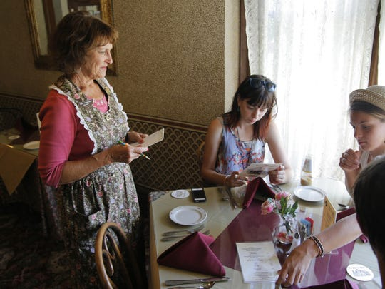 Valley Guild volunteer waitress Thais Winkelman of Boulder Creek helps guests from New York at the Steinbeck House in Salinas on Friday afternoon.
