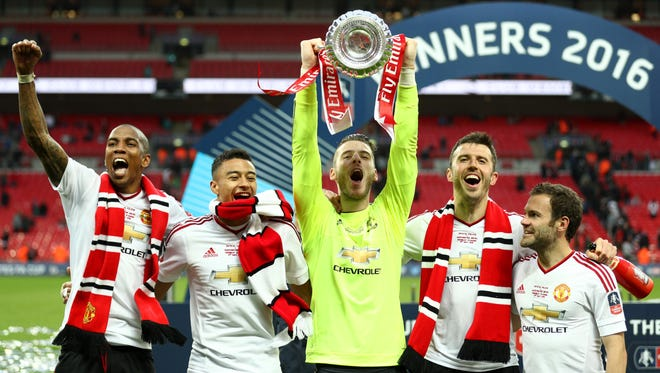 Ashley Young, Jesse Lingard, David De Gea, Michael Carrick and Juan Mata of Manchester United celebrate with the FA Cup trophy.