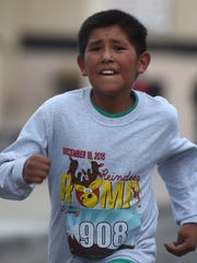 Kody Garcia, 11, finishes the Reindeer Romp & North Pole Stroll on Saturday on Main Street in Farmington.