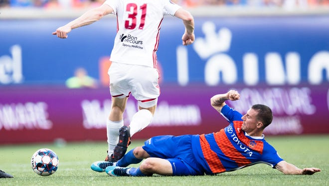 FC Cincinnati midfielder Corben Bone tackles the ball away from Richmond Kickers defender Braeden Troyer (31)