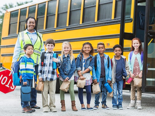 Children and crossing guard standing outside school bus