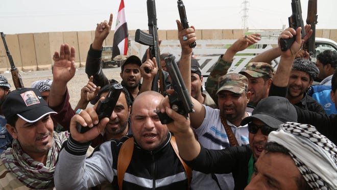 Iraqi Shiite militiamen chant slogans during clashes with the Islamic State group in Tikrit, 80 miles north of Baghdad, on March 13, 2015. On Friday, the Iraqi military fought fierce battles to secure a northern Tikrit neighborhood and lobbed mortars and rockets into the city center, still in the hands of the Islamic State.