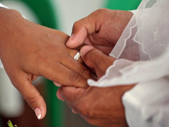 A man places a ring on his wife's finger during a wedding