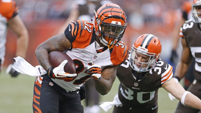Cincinnati Bengals running back Jeremy Hill (32) breaks a tackle by Cleveland Browns defensive back Jim Leonhard (30) to score a touchdown during the second quarter of their game against the Cleveland Browns played at FirstEnergy Stadium in Cleveland.