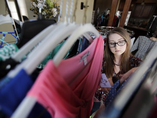 Katie Thoe, a senior at Appleton North High School, arranges dresses Wednesday for the Hello Beautiful resale dress shop.