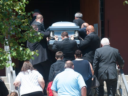 Pallbearers carry the casket into Church of St. Michael