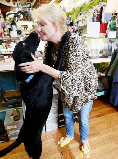 Darby's owner, Darby Short, pets her dog, Mary Francis, at the store located at 410 Main Street in Natchez, MS.