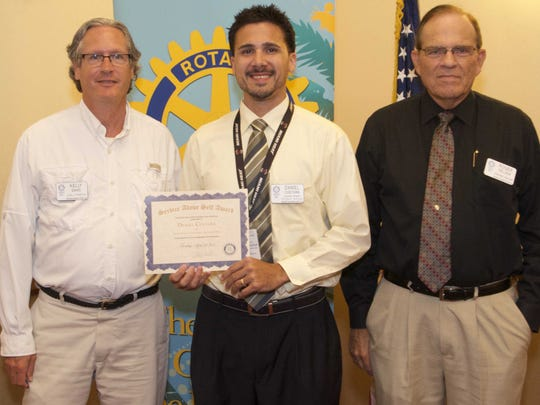 Kelly Davis, president of the Northern Palm Beach Rotary Club, at left, and Roger Pelser, a Rotary club member, at right, recognize Daniel Cuetara, Interact adviser for Palm Beach Gardens High School, center, for his leadership with Interact.