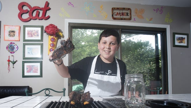 Chef Daniel Marcus, age 12, cooks beef ribs on a grill at his home in Cherry Hill. Daniel was featured on the Food Network Kids BBQ Championship show on June 19.