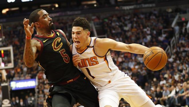 Phoenix Suns guard Devin Booker (1) runs into Cleveland Cavaliers guard JR Smith (5) during the second quarter at University of Phoenix Stadium in Phoenix, Ariz. March 13, 2018.