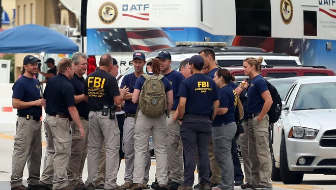 The FBI gather early Monday, in front of  Pulse Nightclub at the mass shooting scene in Orlando. Federal investigators promised to provide more insight as to what was happening inside the Pulse nightclub after a gunman started a deadly assault that was the worst mass shooting in modern U.S. history.