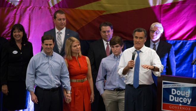 Former Massachusetts Governor and 2012 GOP Presidential Nominee Mitt Romney (right) speaks during Republican gubernatorial nominee Doug Ducey's (left, front) rally at the Mesa Convention Center, 263 N Center St., Mesa, on Oct. 23, 2014.