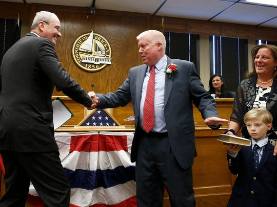 Brick Township Mayor John Ducey is congratulated by Governor Elect Phil Murphy after he took the oath of office from Murphy at the Town Hall Monday January 1, 2018.  Shown with Ducey are his wife Deirdre and son Jack.