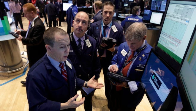 Specialist Jason Notter, left, works with traders at the post that handles BlackRock, on the floor of the New York Stock Exchange, on Jan. 16, 2014.