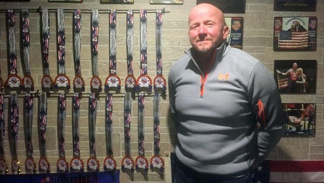 In this Jan. 30,  2017, photo, personal trainer Duane Burlingame stands in his home gym in Freeport, Ill., next to just a few of the medals he's won in weightlifting competitions. Burlingame, 59, has competed in drug-tested weightlifting events all over the United States since 1998. Aside from his 96 world titles, he's captured 28 world cups, 56 national titles and 72 regional titles.