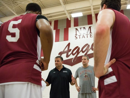 NMSU head basketball coach Chris Jans, second from left, talks with his team during a warm up session on Wednesday at the Pan American Center.