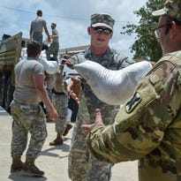 Members of the Louisiana Army National Guard help place sandbags to protect City Hall in Lake Arthur on Wednesday.