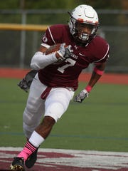 Aquinas's Caron Robinson carries the ball for several yards during a game last season.