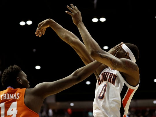 Auburn forward Horace Spencer, right, gets a hand to the face from Clemson forward Elijah Thomas (14) as he shoots during the first half of a second-round NCAA men's college basketball tournament game Sunday, March 18, 2018, in San Diego. (AP Photo/Gregory Bull)