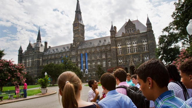 Prospective students tour Georgetown University's campus in Washington, D.C., in July. College costs are an increasing concern for prospective students.