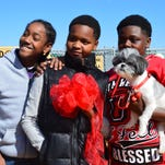 "Jonathan Jones, from left, Martese Brown and TreVon Dixon pose with the ribbon and their dog, Gizmo. Brown won the contest to name the dog park and named it ""Fields of Barktopia."""
