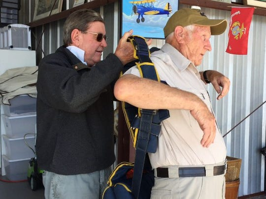 From left, Tom Ackland helps Allan McNeely with his parachute before taking off from Bermuda Dunes Airport in Ackland's 1943 Stearman biplane on Thursday, March 10, 2016.