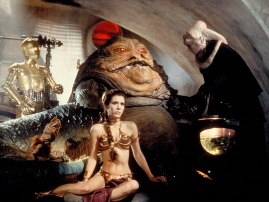 """Jabba the Hutt is the slug-like gangster who made C-3PO (Anthony Daniels, far left) and Princess Leia (Carrie Fisher) his slaves in """"Return of the Jedi."""""""