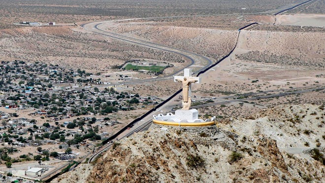 A statue of Christ stands atop Mount Cristo Rey in Sunland Park, N.M. The religious site straddles the border of Mexico and the United States.