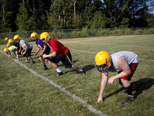Football players line up during conditioning drills