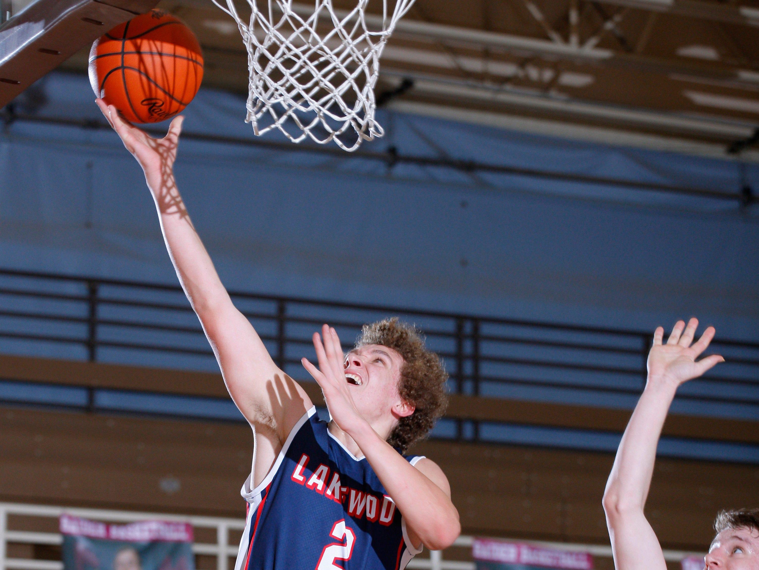 Lakewood's Josh Campeau (2) gets a layup against Portland's Brett Pung, center, and Bobby Brandsen, right, Tuesday, Jan. 31, 2017, at Portland High School. Portland won 53-44.