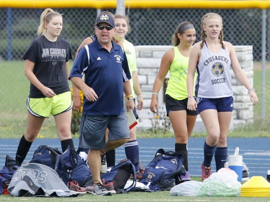 Notre Dame girls soccer head coach Steve Weber leads his team onto the field for the start of practice in August of 2016.