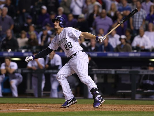 Colorado Rockies' Nolan Areando follows the flight of his walkoff double to drive in two runs against the San Francisco Giants in the ninth inning of the Rockies' 5-4 victory in a baseball game in Denver on Tuesday, May 20, 2014. (AP Photo/David Zalubowski)