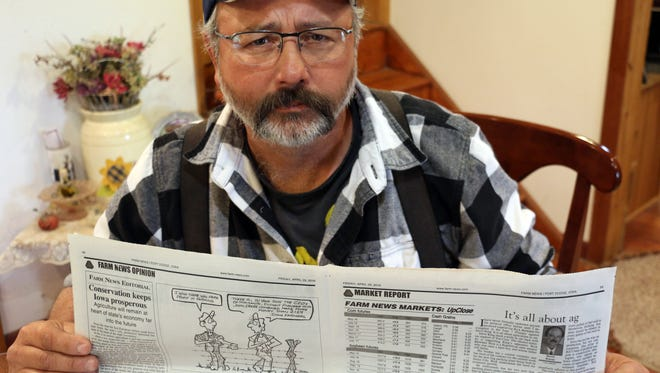 Rick Friday was a cartoonist for 21 years for Farm News but was fired after one of his cartoons angered a seed dealer that advertises in the newspaper. Here he holds the issue that contains his final cartoon.