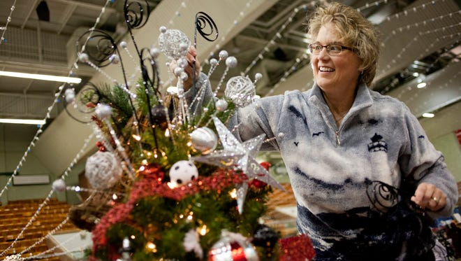Kris Lashbrook, of St. Clair, decorates a tree Wednesday at McMorran Arena for the Festival of Trees.