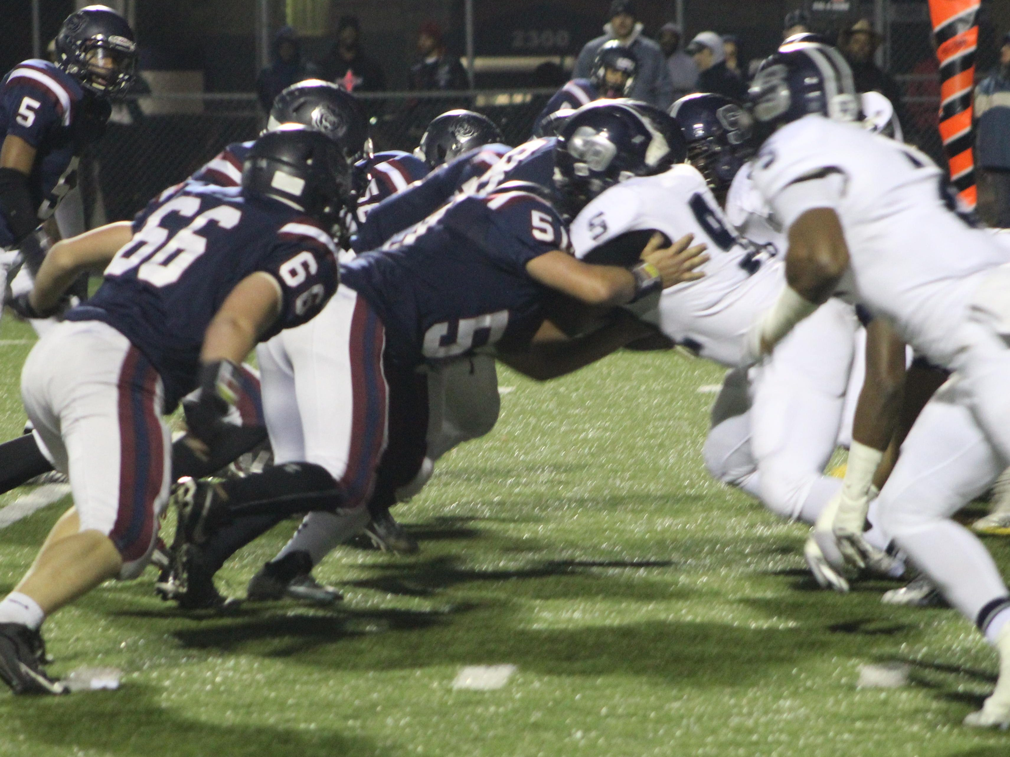 Southfield's defensive line (right) converges to stop Berkley quarterback Ross Herron for a short gain.